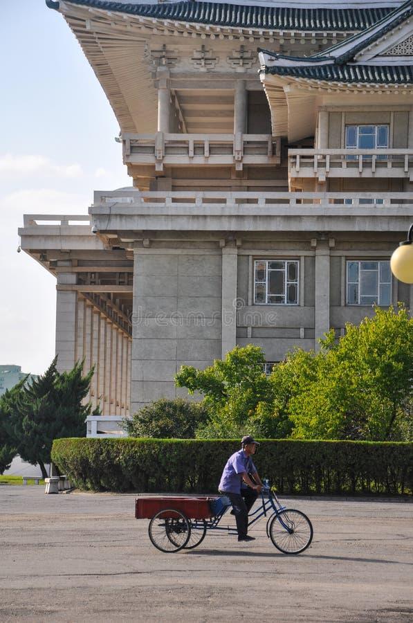 Пхеньян, Север-Корея, 09/07/2018: сиротливый велосипед перетаскивания проходит культурным дворцом людей стоковая фотография rf