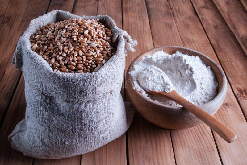 Пшеница в мешке и муке в деревянном шаре с ложками на таблице стоковые изображения rf