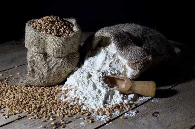 Пшеница и мука в сумках джута на старом деревянном столе над черной предпосылкой стоковые фото