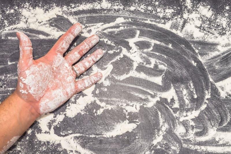 Пшеничная мука на серой рабочей поверхности с мужской рукой стоковые фотографии rf
