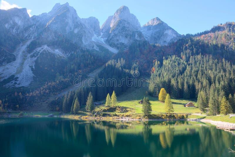 Пышный пейзаж осени озера Gosausee с изрезанными скалистыми горными пиками на заднем плане и красивыми отражениями на воде стоковое фото