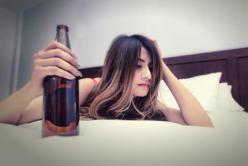 Пьяная женщина на кровати с бутылкой стоковые изображения rf