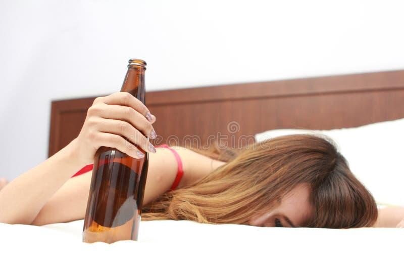 Пьяная женщина спать на кровати с бутылкой лозы внутри стоковые фото