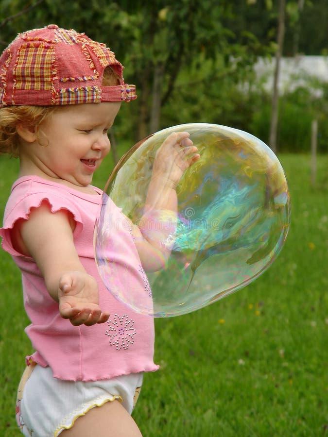 Пятилетние игры девушки с пузырем мыла стоковое фото rf