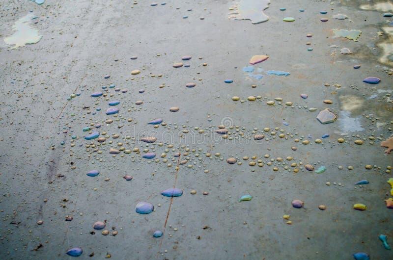Пятна радуги химические на воде в лужице на дороге стоковое фото