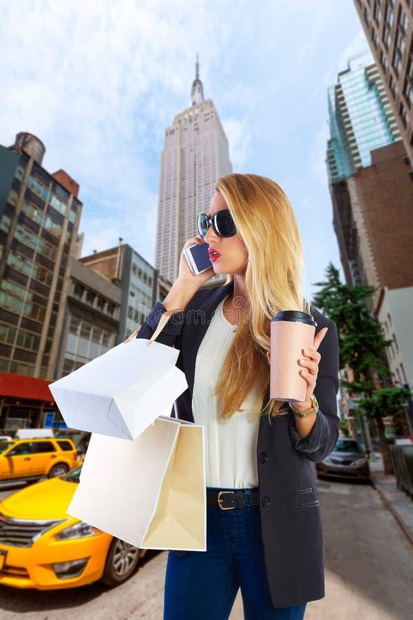 Пятый авеню NY телефона белокурой девушки shopaholic говоря стоковая фотография