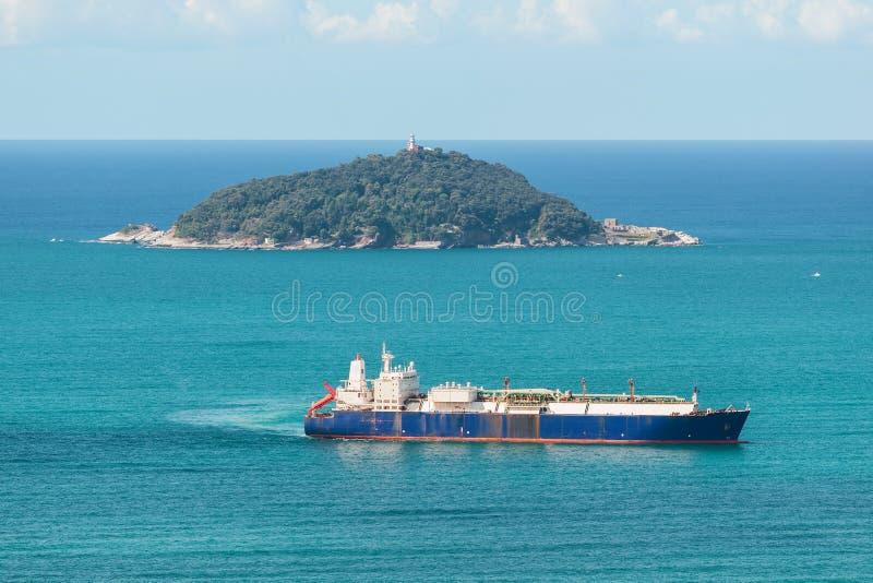 Плавание корабля топливозаправщика в море вдоль острова стоковые изображения