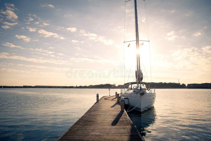 Плавающ яхта причаленная к пристани на заходе солнца стоковое фото rf