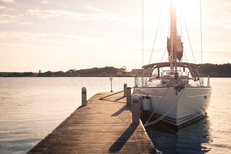 Плавающ яхта причаленная к пристани на заходе солнца стоковая фотография