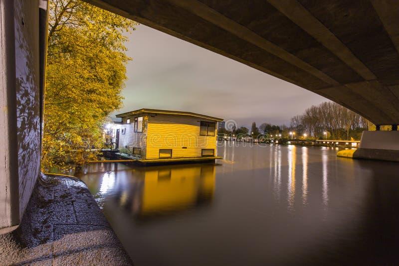 Плавучий дом расположенный под мост в реке Amstel в Амстердаме стоковые фотографии rf