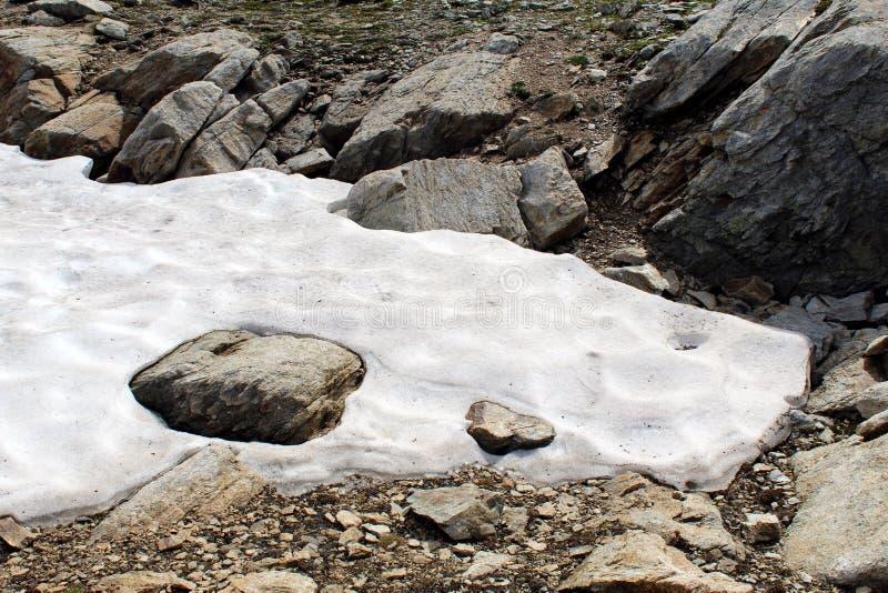 Плавя снег между утесами стоковое фото