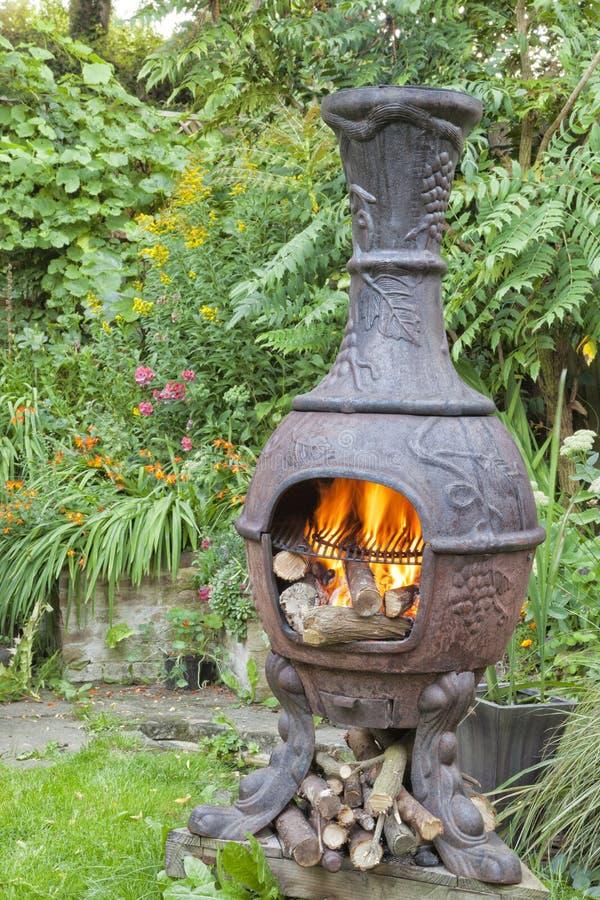 Пламена деревянного огня в барбекю сада chiminea стоковое фото rf