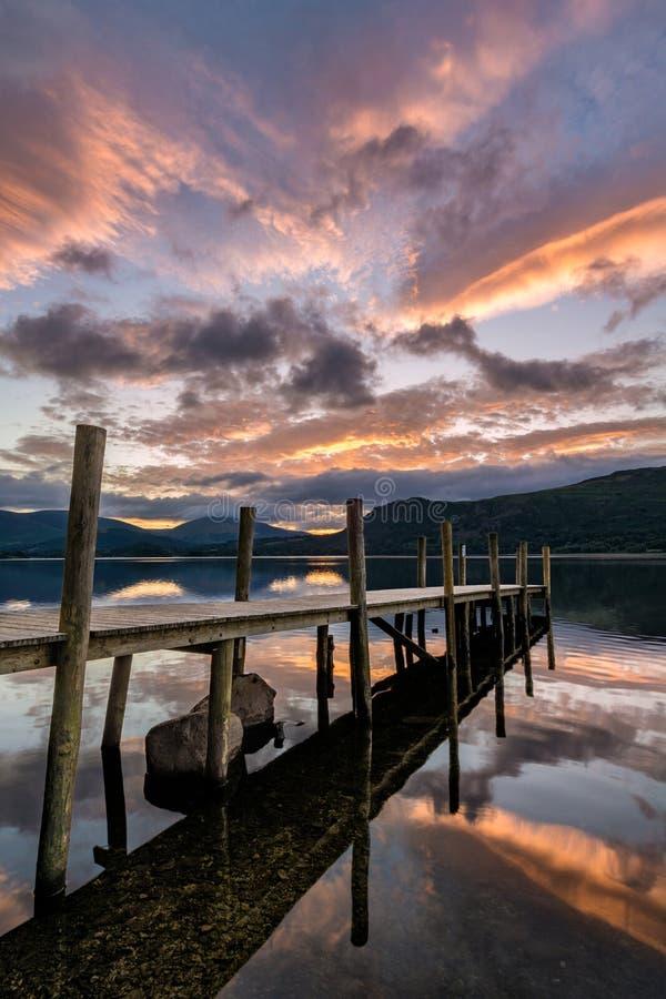 Пламенистый оранжевый восход солнца над молой озера стоковое фото rf