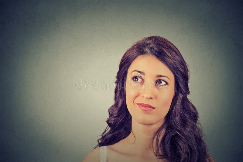 Планирование confused скептичной женщины думая смотря вверх стоковое фото