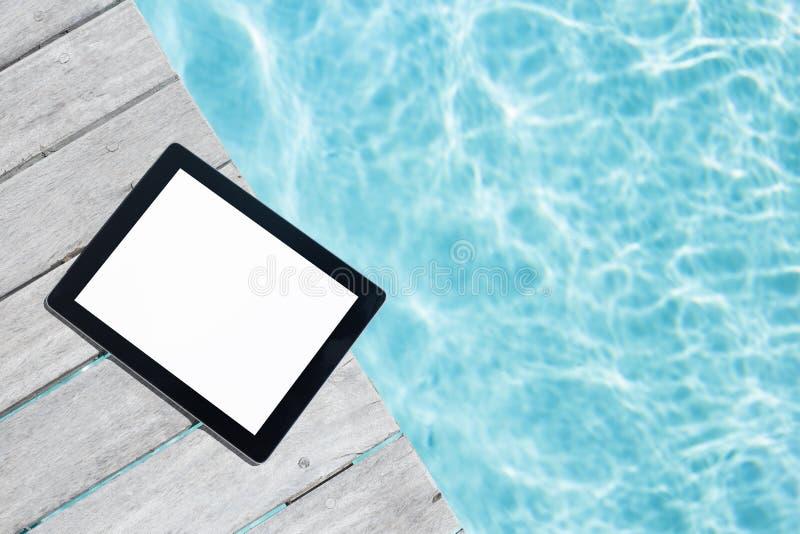 Планшет с пустым экраном на деревянной палубе бассейна стоковое изображение