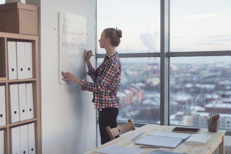 План дня сочинительства коммерсантки на белой доске магнита, современном офисе Взгляд со стороны кавказского женского планировани стоковые изображения rf