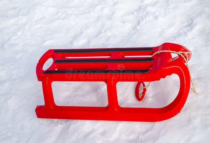 Пластичные красные сани с черным двором оправы в зиме стоковые изображения rf