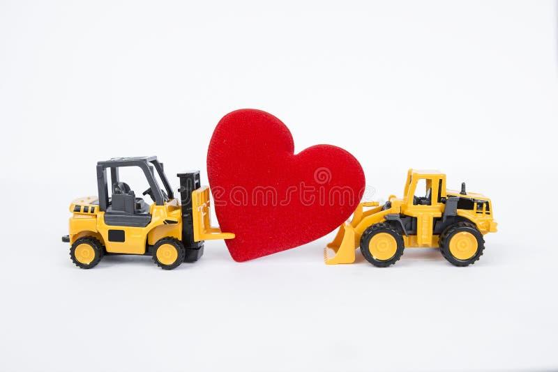 Платформа грузоподъемника и передний затяжелитель перевозят moving красное сердце на грузовиках стоковое изображение
