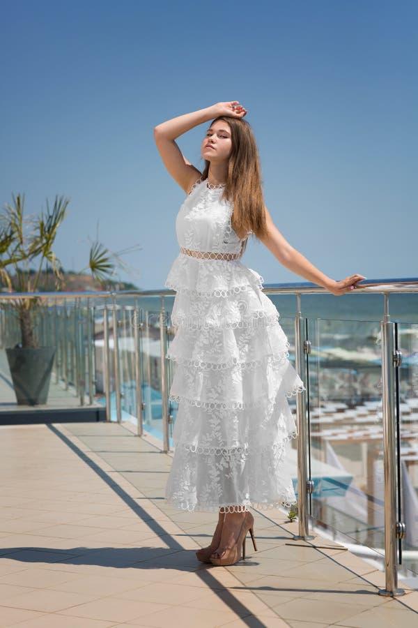 Платье дамы внутри длинное, белое и на высоких пятках на балконе ` s гостиницы Брюнет в элегантном платье на предпосылке голубого стоковая фотография