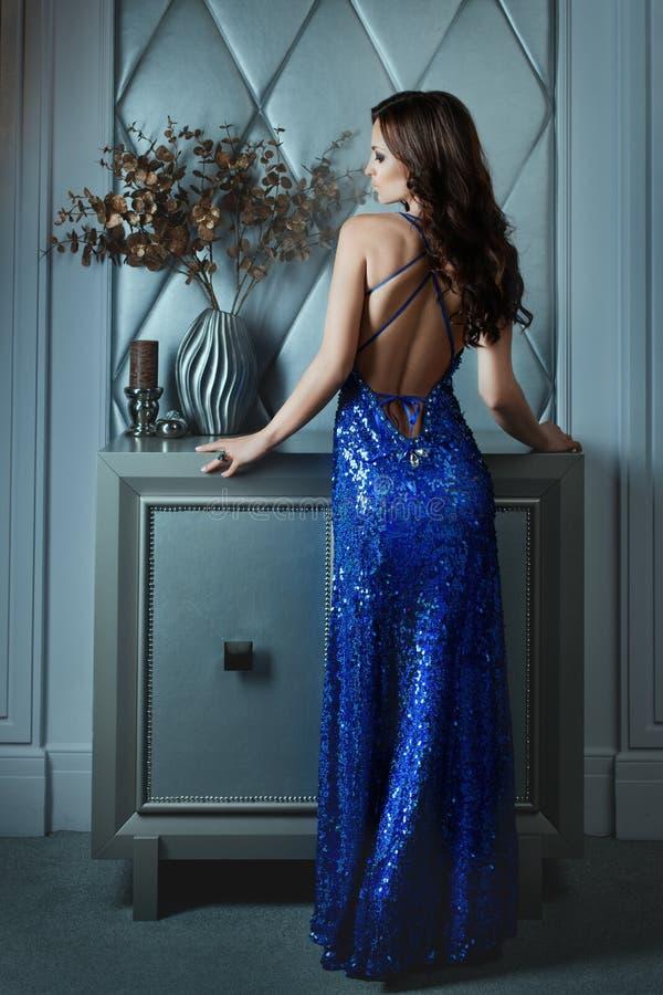 Платье женщины с чуть-чуть задним положением в темной комнате стоковое изображение