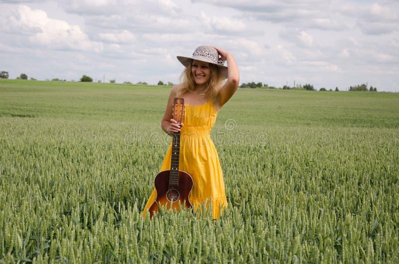 Платье и гитара желтого цвета женщин представляют в поле рож стоковые изображения