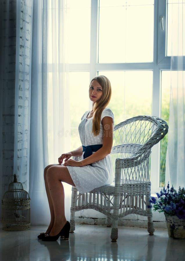 Платье милого брюнет нося белое представляя на кресле стоковое фото
