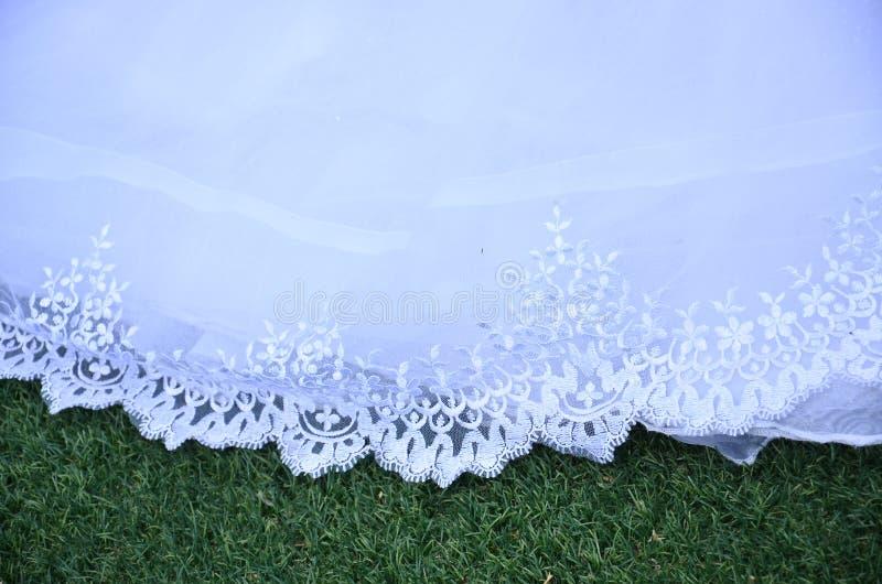Платье свадьбы шнурка Hemline белое на зеленой траве стоковое изображение