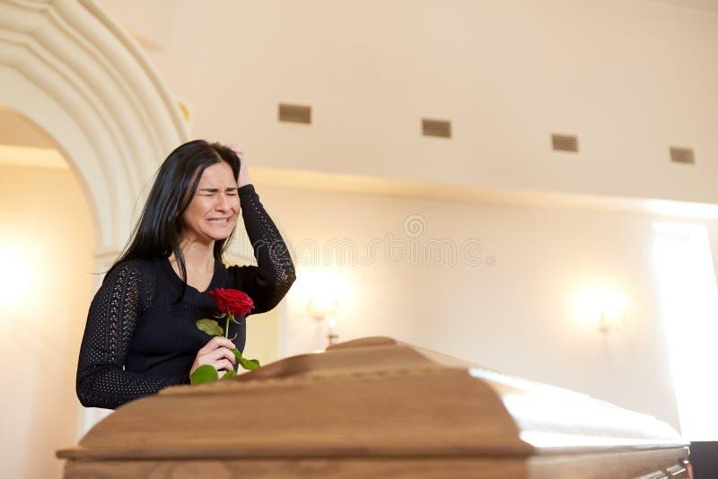 Плача женщина с красной розой и гробом на похоронах стоковые фотографии rf