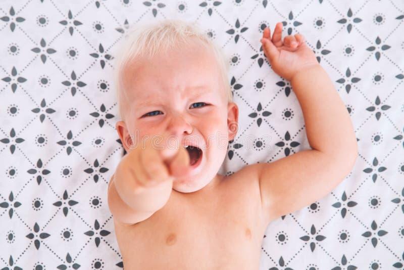 Плача сердитый мальчик в кровати стоковые фото