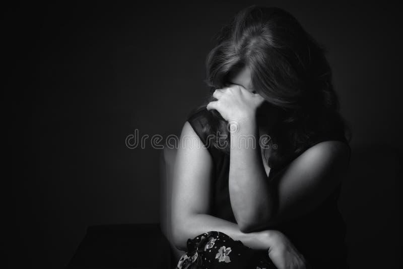 Плача унылая женщина на черной предпосылке стоковые фото