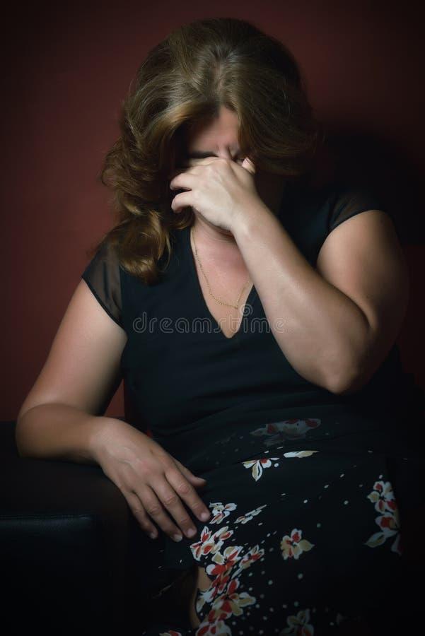 Плача унылая женщина самостоятельно в темноте стоковые фото