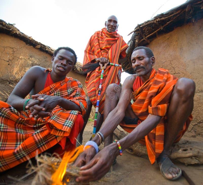 Племя Masai людей делает огонь в традиционном пути стоковое фото