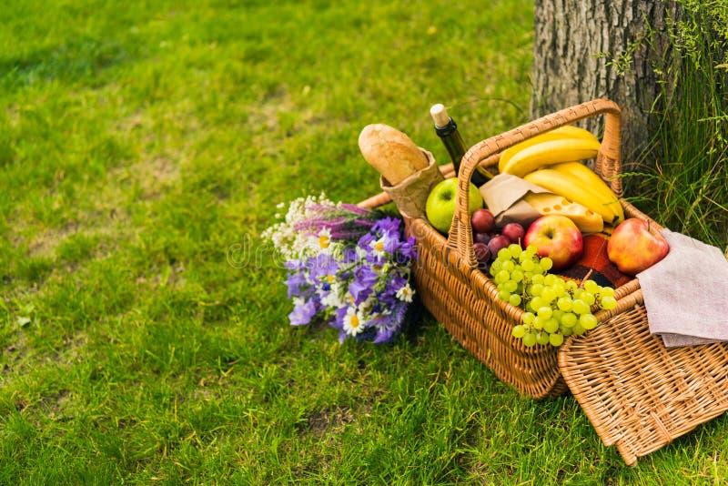 Плетеная корзина пикника с плодоовощами и вином, сыром, багетом и букетом красивых цветков стоковая фотография