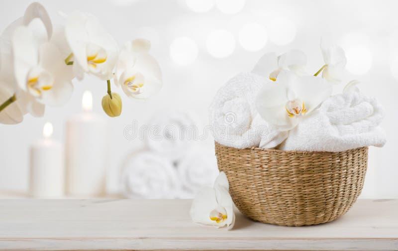 Плетеная корзина с полотенцами курорта на таблице над абстрактной предпосылкой