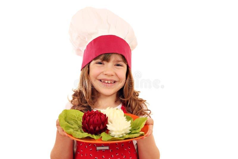 Плита владением кашевара маленькой девочки с украшенным салатом любит lotu стоковое изображение rf