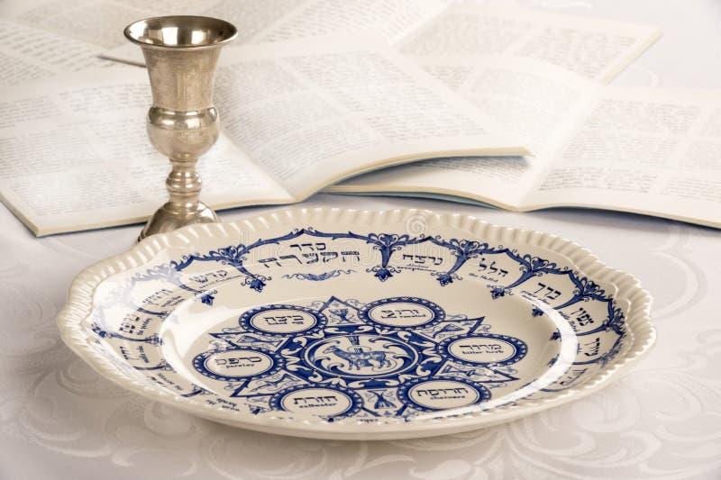 Плита еврейской пасхи с чашкой и Haggadah Kiddush стоковое изображение