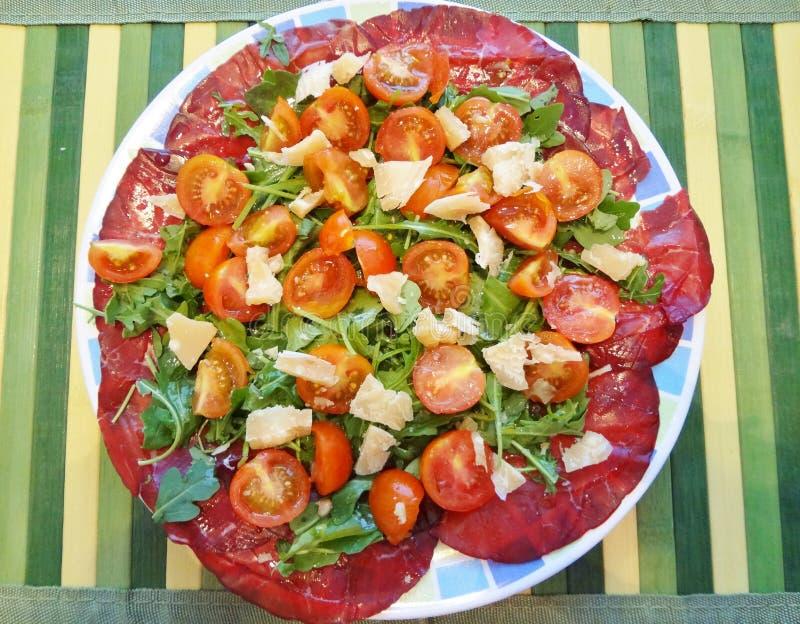 Плита лета: листья ракеты, высушенное мясо, пармезан и томаты стоковые изображения rf