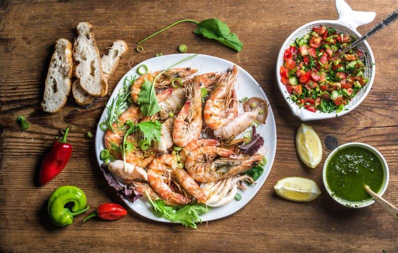 Плита зажаренных в духовке морепродуктов с свежим лук-пореем, зеленым салатом, перцами, лимоном, хлебом, соусом песто над деревян стоковое фото rf