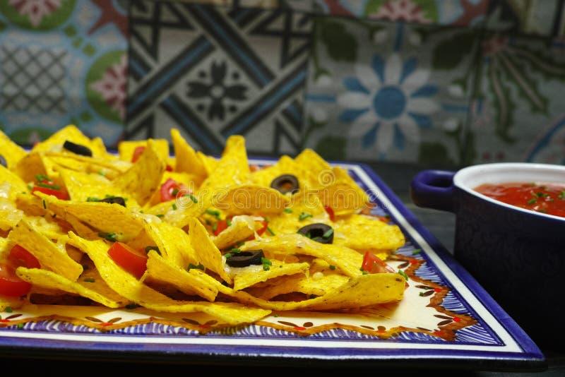 Плита очень вкусных nachos tortilla с расплавленным соусом сыра, c стоковое фото rf