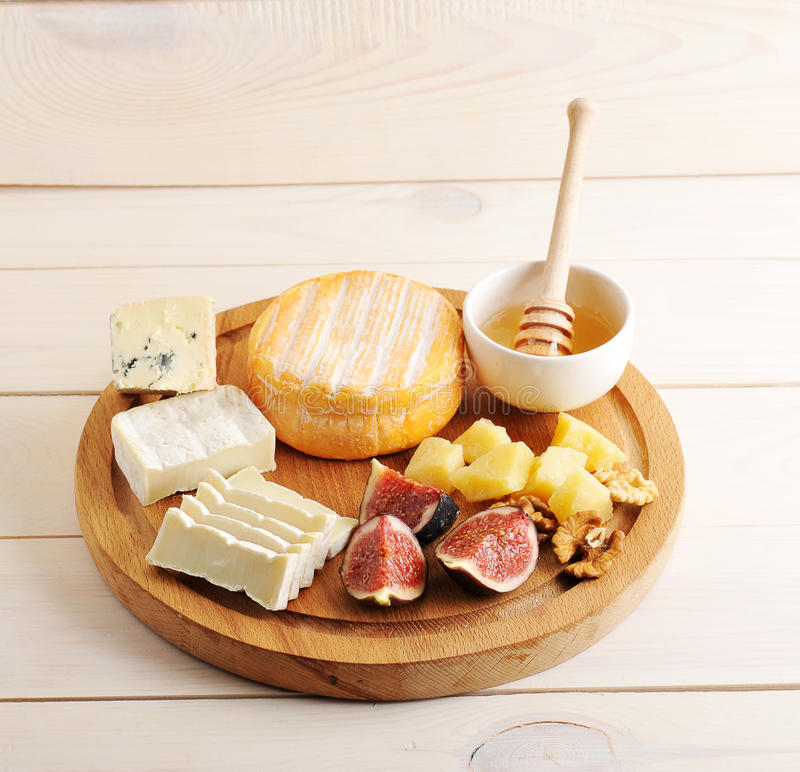 Плита сыра - различные типы сыра, меда и смокв стоковое изображение rf