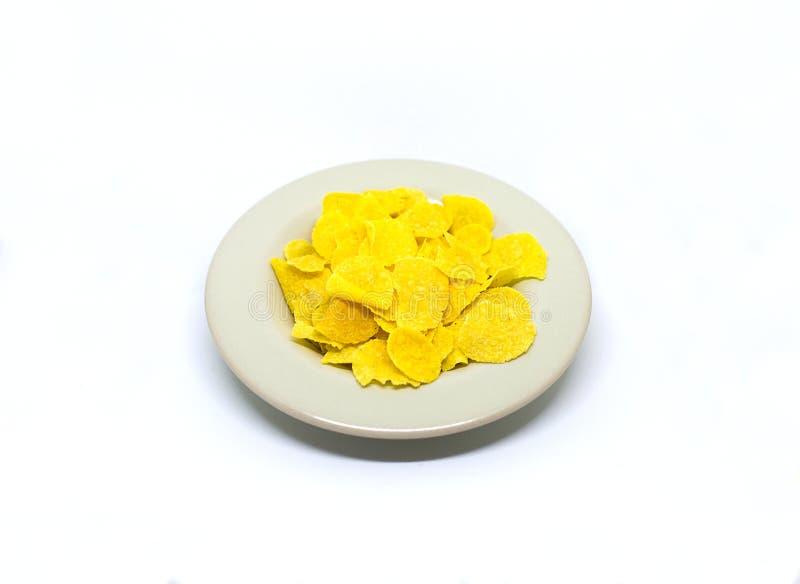 Плита с желтыми закусками мозоли шелушится на белой предпосылке стоковое фото
