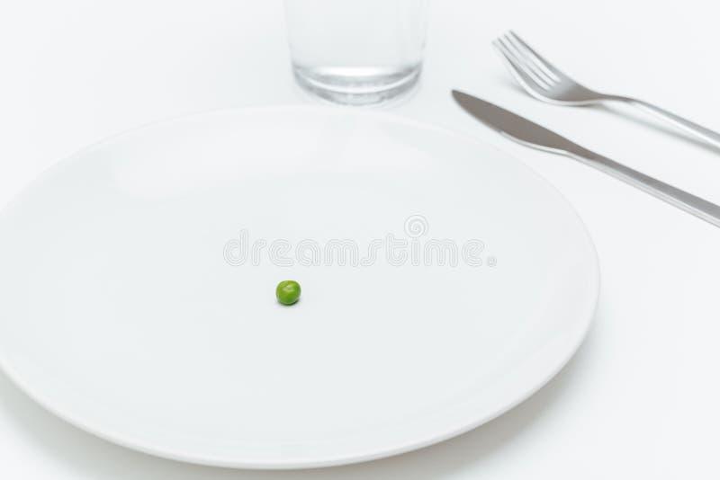 Плита с одним малым зеленым горохом на, который служат таблице стоковые фото