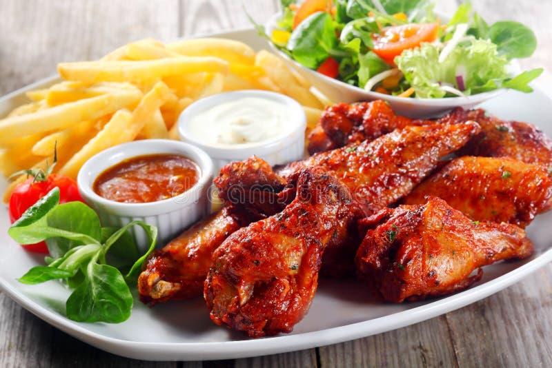 Плита для главным образом закуски с кудрявыми Drumsticks жареной курицы стоковая фотография