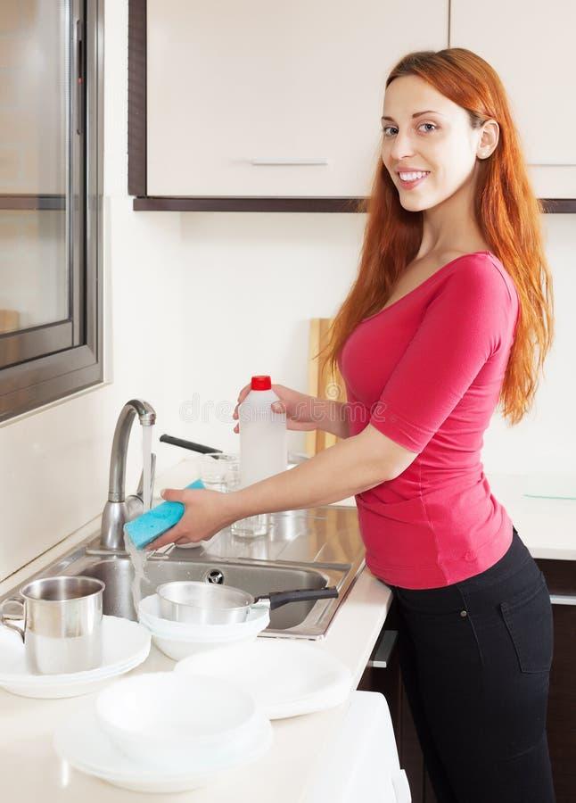 Плиты положительной домохозяйки моя с губкой стоковое изображение