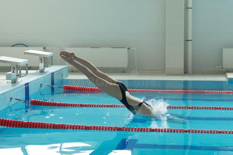 Пловец маленькой девочки, тот скакать и нырять в бассейн крытого спорта стоковое изображение rf
