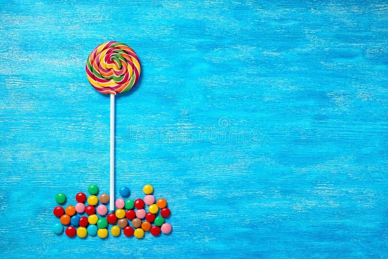 Плоское положение красивого пестротканого леденца на палочке и сладостных bonbons дальше стоковые фотографии rf