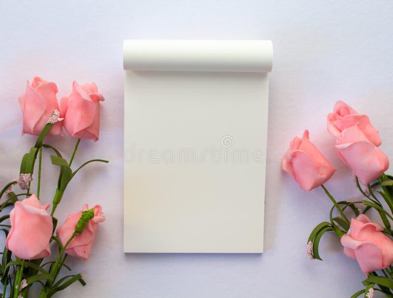 Плоское положение с блокнотом и розами на белой предпосылке Романтичный шаблон знамени с местом текста стоковые изображения rf