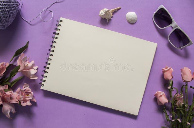 Плоское положение с розами и seashells на фиолетовой предпосылке Романтичный розовый букет цветка стоковая фотография rf
