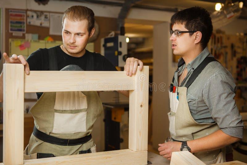 Плотники работая с деревянными планками на мастерской Люди строя деталь стоковое изображение rf