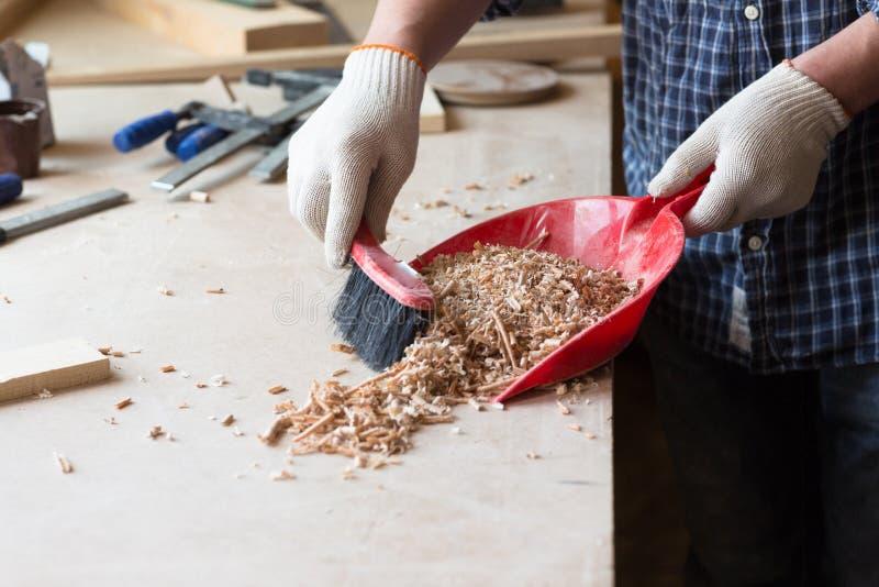 Плотник в мастерской плотничества подметает опилк, стоковые фото